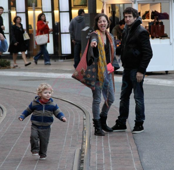 EXCLUSIVE: Marion Cotillard kisses her partner Guillaume Canet while enjoying a day out with their son Marcel at the Grove in Hollywood, CA. Pictured: Marion Cotillard, Marcel and Guillaume Canet Ref: SPL486377  240113   EXCLUSIVE Picture by: Zodiac / Splash News Splash News and Pictures Los Angeles:310-821-2666 New York:	212-619-2666 London:	870-934-2666 photodesk@splashnews.com